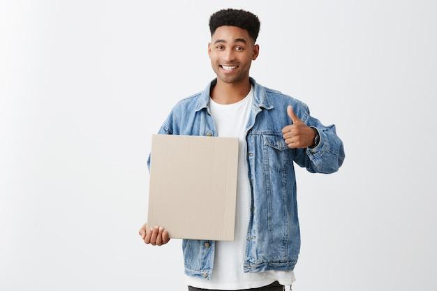 スペースをコピーします。幸せで満足した表情で親指を現してカートンを手に持っているスタイリッシュなカジュアルな服装でアフロの髪型を持つ陽気な若い黒肌の男性学生のクローズアップ