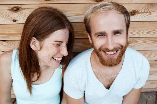若い美しいカップル笑顔、木の板の背景にポーズ