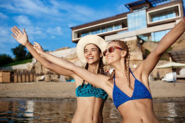 喜び、笑みを浮かべて、海岸で笑って水着の若い美しい女性