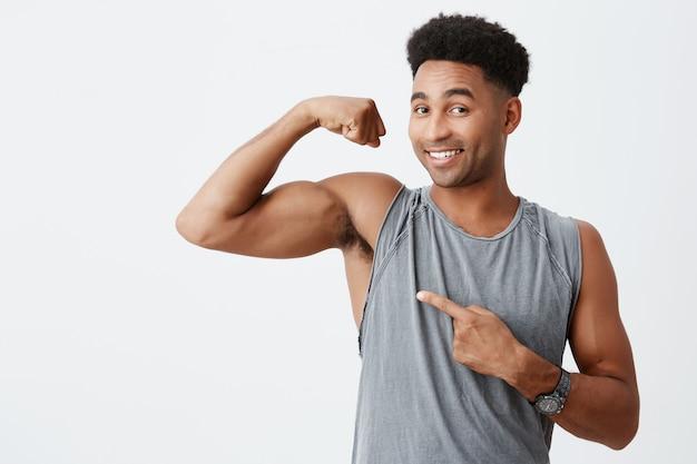 スポーツとライフスタイルのコンセプトです。筋肉を示す巻き毛を持つ暗い肌のハンサムな男。幸せな表情でスポットキャリアについての記事にポーズをとってプロスポーツマン