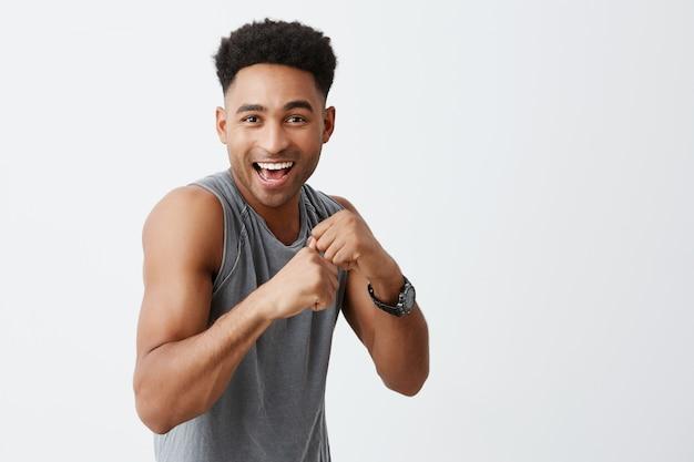 スポーツは楽しいです。スポーティな灰色のシャツで明るくアフロの髪型と陽気な美しい黒い肌の男性の肖像笑顔、大学新聞の写真撮影のためにポーズ、スポーツが健康で楽しいことを示す