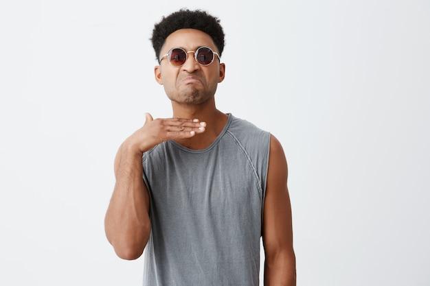 Ты будешь мертв, чувак. молодой привлекательный агрессивный афро-американский мужчина студент с вьющимися волосами в спортивной рубашке и солнцезащитные очки, жестикулируя рукой, будучи подлым своему другу после аргумента