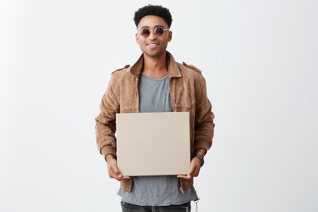 幸せな表情でカメラで探している灰色のシャツ、茶色のジャケット、サングラスを手に明るい笑顔の板紙を手に持つアフロ髪の若いハンサムな浅黒い肌の男の肖像画。