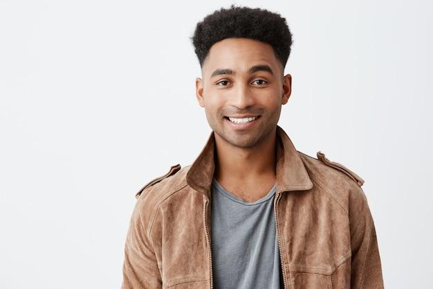 Закройте вверх изолированный портрет молодого темнокожего привлекательного парня с афро стилем причёсок в серой футболке под коричневой курткой усмехаясь при зубы смотря в камере с счастливым и мирным выражением стороны.