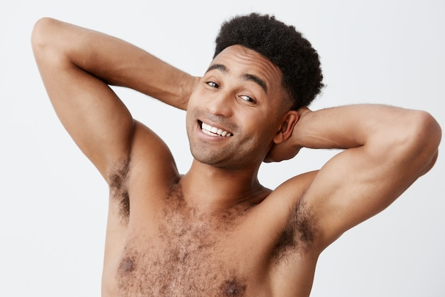 , копировать пространство спа, концепция релаксации. крупным планом веселый привлекательный зрелый спортивный темнокожий человек с афро прическа без одежды, улыбаясь, держась за руки за голову.