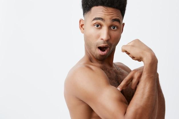 この筋肉を見て、赤ちゃん。自信を持って、軽薄な表情でカメラを見ている彼の腕を指しているアフロの髪型を持つ若い浅黒い美しいハンサムな運動男。