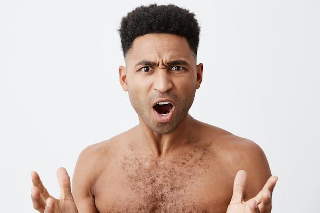 一体何ですか。彼のお気に入りのサッカーチームが試合に負けたとき、混乱した表情で手を広げて服のない巻き毛の美しい黒肌の男のクローズアップ