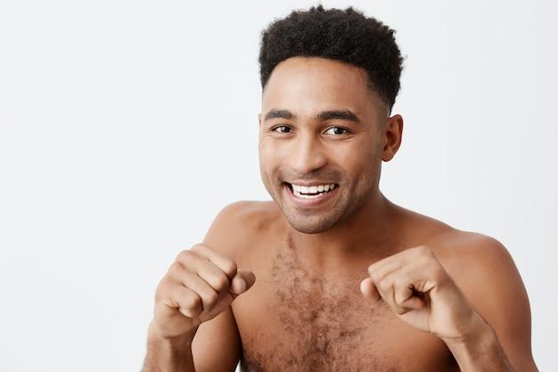 雑誌のフォトセッションのポーズの戦いのポーズで立っている暗い巻き毛を持つプロのアスレチックアフリカ浅黒いボクサーの肖像画を閉じます。スペースをコピーします。