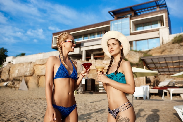笑みを浮かべて、海のビーチでジュースを飲んで水着で美しい女性