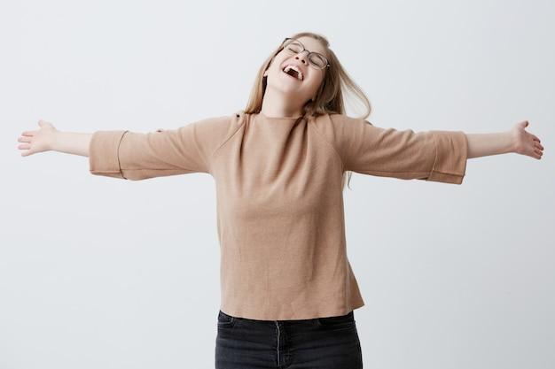 Веселая молодая женщина в очках со светлыми прямыми волосами, громко смеется, веселится в помещении, закрывает глаза и поднимает руки, танцует