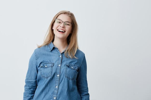 若者、ライフスタイル、教育の概念。ブロンドの髪と幅広い笑顔、笑い、家で休んでいる間見て、トレンディな眼鏡とデニムシャツを着てかわいい学生の女の子
