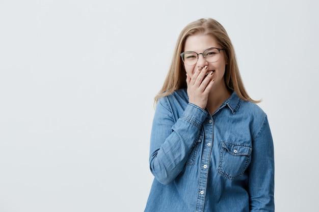 人間の顔の表情と感情。面白い冗談を真剣に笑って、カメラを見て、デニムシャツとメガネを着て、手のひらの後ろに顔を隠して若い陽気で魅力的なブロンドの女性