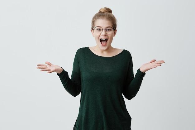 Удивленная счастливая белокурая девушка, одетая небрежно в очках, восклицая от волнения и пожимая плечами в полном недоумении после того, как получила неожиданные позитивные новости. язык тела