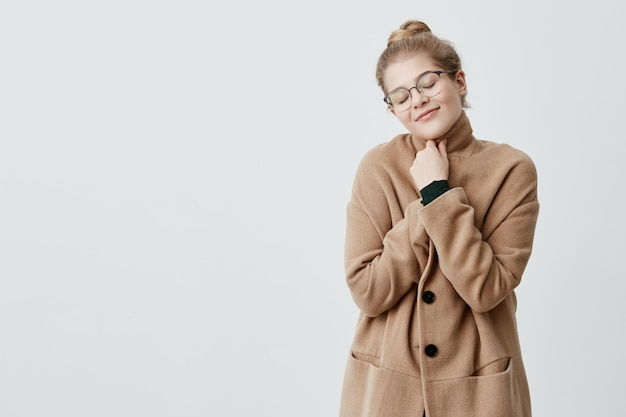 喜びのポーズで目を閉じて、誠実で満足のいく笑顔でコートに身を包んだ結び目でブロンドの髪を持つ安らかな女性の写真。幸せな女性の喜びの生活