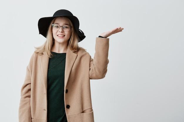 若い女性の不幸、開いた手のひらで身振りで示す、見上げる、うんざりしている、外出したいが雨が怖い。悪天候のためコートと帽子をかぶった女子学生が戸惑いました。