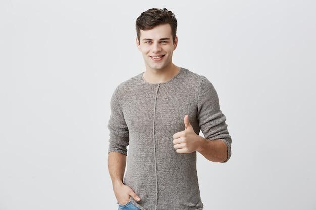 私はすきです。よくやった。黒髪の幸せな白人男性。カジュアルな長袖のセーターを着て、親指を立てて元気に笑って、誰かへのサポートと敬意を示しています。ボディランゲージ
