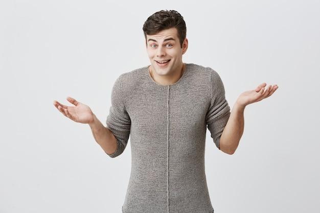 セーターにトレンディな髪型をした混乱した白人男性は肩をすくめ、彼の人生で困難な選択をし、何をすべきかわからないので、困惑して手のひらを開いたままにします。人生の認識と態度。
