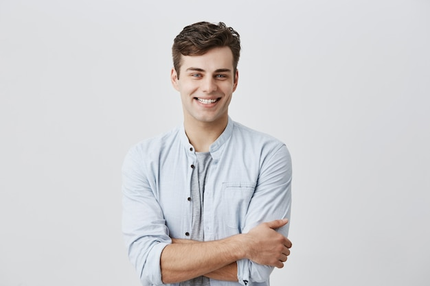 人とライフスタイルのコンセプトです。陽気な完璧な白い歯を見せて笑顔の青い長袖シャツを着た、機嫌の良い魅力的な若い白人男性。