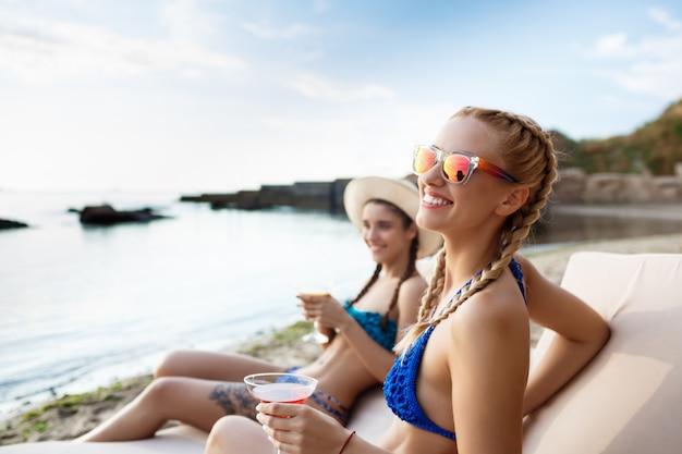 笑顔、日光浴、海の近くの長椅子で横になっている若い美しい女性