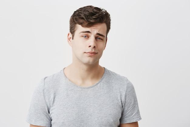 格好良いスタイリッシュなハンサムな男性のポーズ。黒髪でさりげなく着こなし、青い目をした魅力的な白人男性は、思慮深い表情をしています。