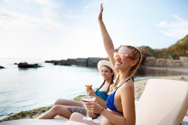 笑顔、挨拶、海の近くの長椅子で横になっている若い美しい女性