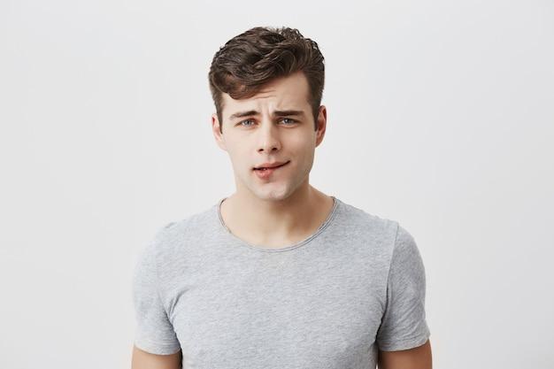 困惑した困惑した男は、思慮深い表情で見たスタイリッシュな散髪でカジュアルに服を着て、唇を噛み、決断を迫られたために落ち込んでしまいました。