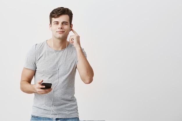 Привлекательный молодой человек в серой футболке с приятным видом держит мобильный телефон в руке, надев белые наушники, с радостью слушает любимые песни, используя музыкальное приложение.