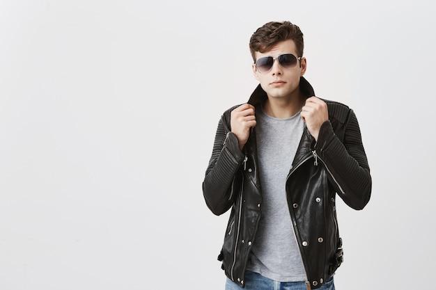 Солнечные очки мышечного уверенно мужчины нося представляя внутри помещения. привлекательный красавчик с модной стрижкой в черной кожаной куртке и джинсах, подтягивая с поднятой рукой куртку, смотрит с привлекательностью