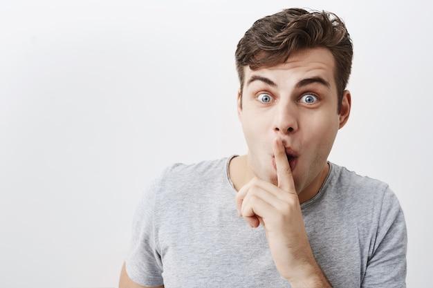 正の変な男は口に人差し指を置き、ポップの目で沈黙の兆候を示し、人々に静かにして顔を作るように求めます。若い男性モデルは秘密を知らない、楽しい、屋内でのジェスチャーを言わない