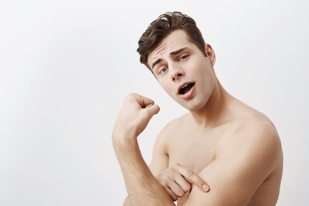 黒い髪と青い目を持つ若い肯定的な筋肉男は、分離されたジムでトレーニング後の上腕二頭筋を示しています。ハンサムな白人男性は強さを誇り、強い男の手を示しています