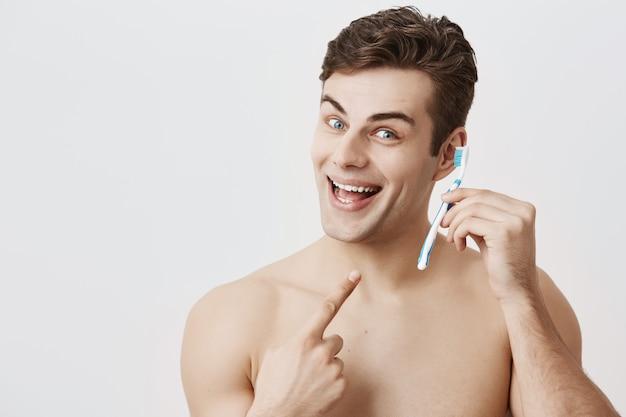 健康的な肌の見栄えの良い筋肉質の男、早く目が覚めた、広く笑った、室内で楽しんでいる、歯ブラシを携帯電話として使うふりをして、人差し指で歯ブラシに向けている。
