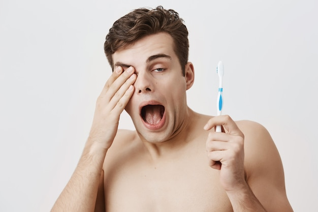 トレンディなヘアスタイルの格好良い眠そうな男子学生。朝早く起きて、仕事や大学の準備をしています。あくびをし、歯ブラシを手に持って、目をこすりながら筋肉質の男。