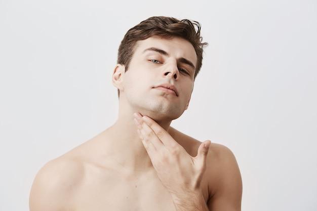 純粋で健康的な肌、スタイリッシュなヘアカットを備えた自信を持って裸のハンサムな男は、あごに手をかざし、彼が剃られているか、孤立しているかをチェックします。人とライフスタイルのコンセプトです。