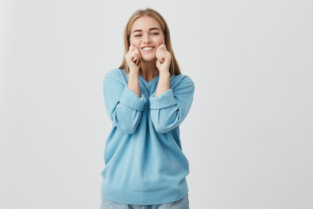 真っ青なセーターとジーンズを着て、笑顔で頬をつまんで笑顔の美しい、魅力的なヨーロッパの女性。かなり、遊び心のある女の子がポーズします。