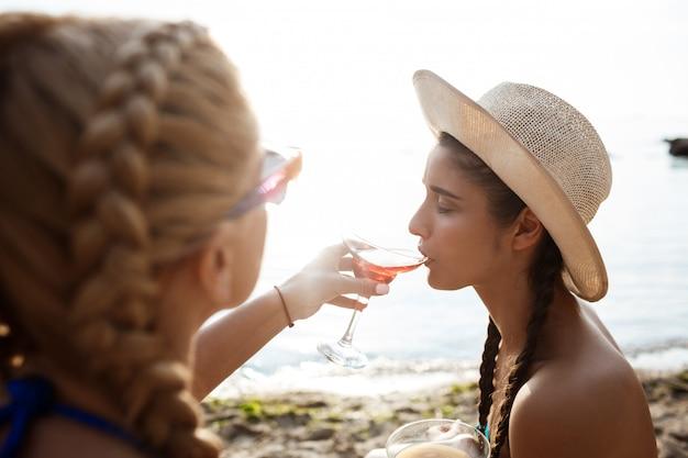 海のビーチでジュースを飲んで水着の若い美しい女性