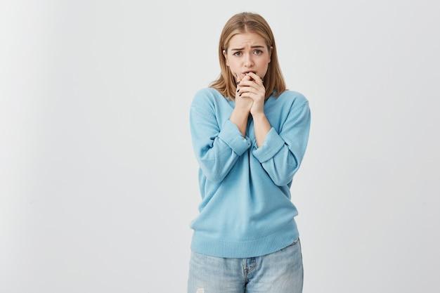 Расстроенная девушка, одетая небрежно, держась руками за подбородок, боится того, что сделала. удивленная светловолосая девушка сожалеет о своих действиях, опасаясь допущенных ошибок