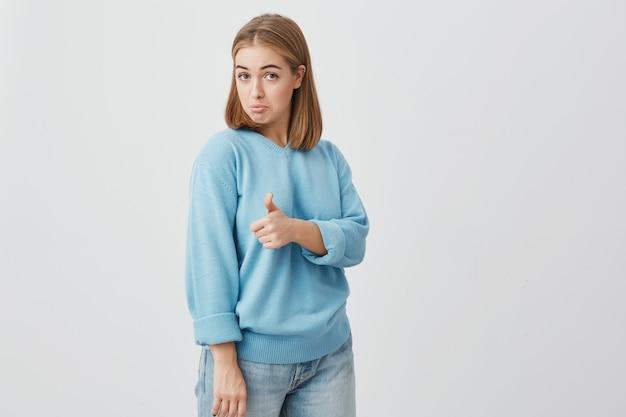 青い服を着た色白の髪の彼女の親指をあきらめて、製品がいかに優れているかを示す興奮した感情的な若いヨーロッパの女性客。ジェスチャーとボディランゲージ
