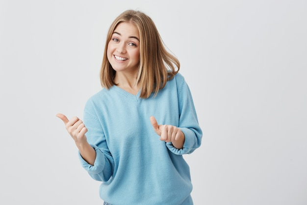 Эмоциональная счастливая молодая кавказская женщина с светлыми волосами одела в голубых одеждах давая ее большие пальцы руки вверх, показывая насколько хорош продукт. красивая девушка, улыбаясь бродли с зубами. жесты и язык тела