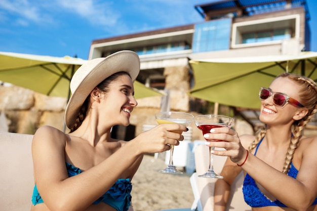 笑みを浮かべて、海辺でジュースを飲んで水着の若い美しい女性