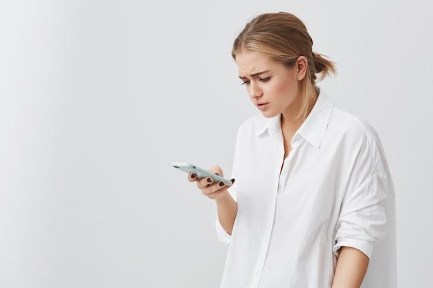 Люди и современное общение. портрет студии потревоженной довольно белокурой девушки читая срочное текстовое сообщение через умный телефон. молодая женщина смотря смущенный держащ сотовый телефон в ее руке.