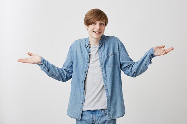 Снимок улыбающегося молодого мужчины носит джинсовую одежду со светлыми волосами, жестами руками, говорит: кого это волнует, я ничего не знаю, имеет возмущенное выражение, позирует на сером фоне студии.