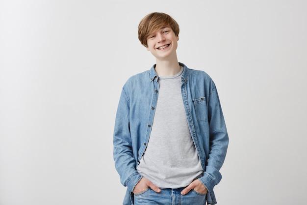 公正な髪と青い目を持つ優しい探している肯定的なヨーロッパの若い男、ブレースで広く笑って、友達との素敵な会話中に、冗談で笑って、立っています。