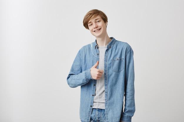 公正な髪と青い目を持つ白人男性の肖像画を間近に着てデニムシャツを着て、親指を上にして、分離されたイヤホンでオーディオトラックを聴いて楽しみながら笑顔
