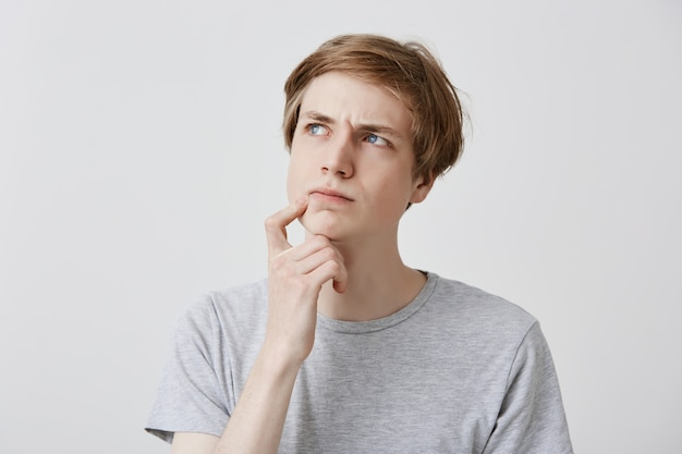 顔の表情、感情、感情。思慮深く懐疑的な表情で見上げ、あごに指を当て、重要なことを思い出そうとする若い金髪の青い目の男