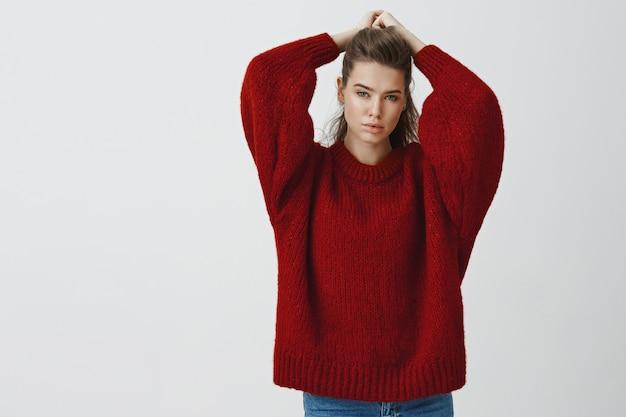 魅力的なスタイリッシュな白人女性モデルはリラックスした官能的なポーズで頭を後ろに手を上げて緩い暖かいセーターで官能的な抱擁生意気な生意気なポーズ
