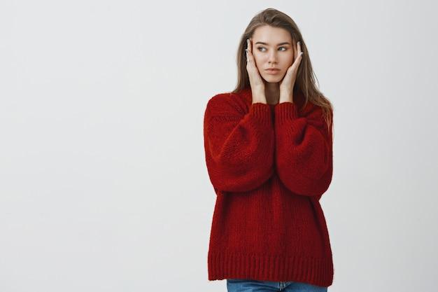 美容、美容、ライフスタイルのコンセプト。魅力的なスタイリッシュで生意気な大人の女性モデル、緩い赤いスタイリッシュなセーターの肌に触れると左に目を向け、マスクを適用した後の滑らかな肌を楽しむ