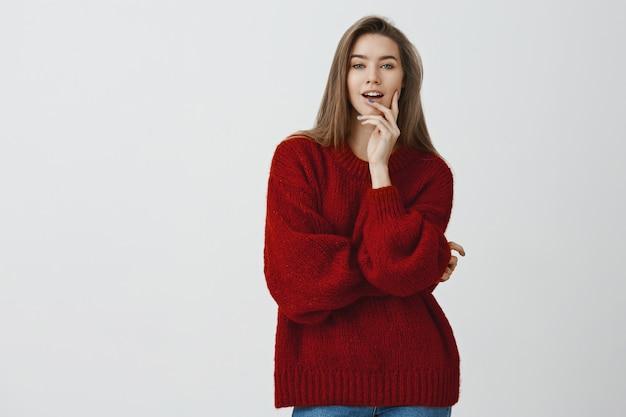 自信を持って見栄えの良い生意気なセクシーなヨーロッパの女性は赤いルーズセーターを噛んで指を大胆で軽薄に見ています。