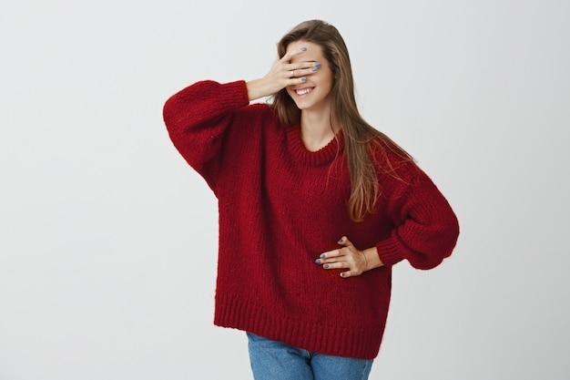 今見てもいいですか。奇妙で興奮した魅力的な女性がトレンディなルーズな赤いセーターを着て目を手で覆い、興奮して笑顔で半分向きを変えて立っている