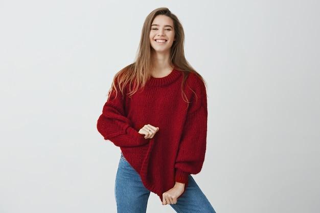 Я купил его в продаже. эмоциональная беззаботная женщина в стильном наряде смотрит счастливой и довольной, в то время как позирует и улыбается, растягивая свитер, стоя. я получил хороший отзыв