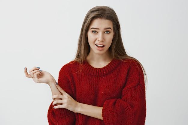Студийный портрет сомнительной не поддавшейся эмоциям симпатичной подруги в модном свободном свитере, жестикулирующей головой и поднимающей бровь с недоверием, слышащей чепуху, выражающей презрение над серой стеной